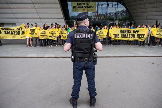 Policeman in Front of Activists during Action at Total's AGM in Paris