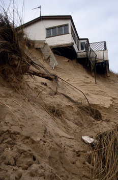 Holiday chalet in danger of collapse as high tides and wave pressure  erode the sand, Hemsby, Norfolk. East coast England.