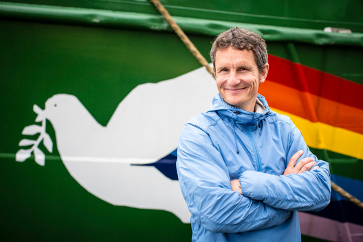 Truls Gulowsen in front of Arctic Sunrise in the Barents Sea