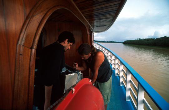 Crew working on radio aboard Greenpeace boat Comandante Savio on Tapaua river during Deni demarcation expedition. Amazon, Brazil