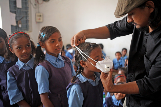 Greenpeace India Activist helping Children to wear N95 Respirator