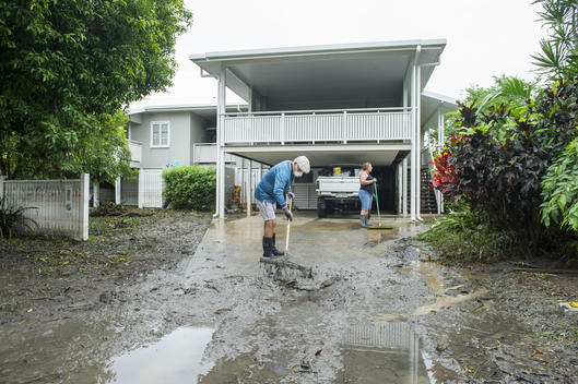 Man Sweeping Flood Water in his Front Yard