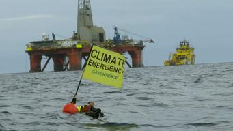 Swimmer in front of BP Oil Rig Holds Climate Emergency Banner- North Sea - News Access