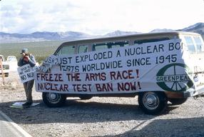 Car van with banner with text  against nuclear testing. Nevada desert.