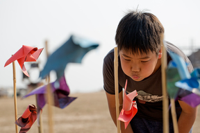 Boy Plays with Windmills at Wonderfruit Festival in Thailand
